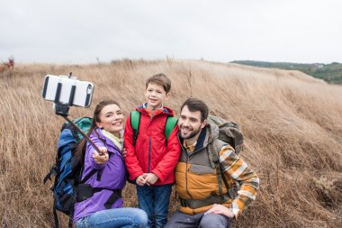 Happy family with backpacks taking selfie