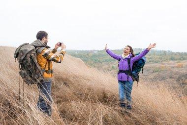 Man photographing woman during walking tour