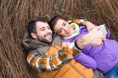 Happy couple taking selfie in grass