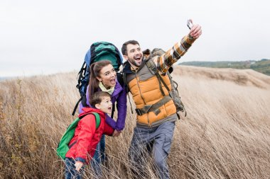 Happy family with backpacks making selfie