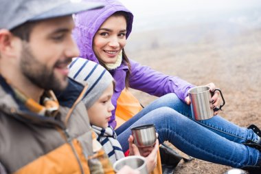 Family drinking tea from metal cups