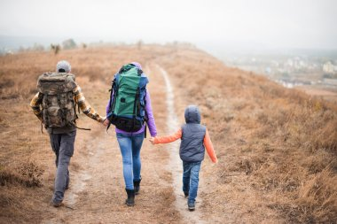 Family with backpacks walking on rural path