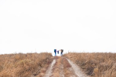 Family with backpacks running on rural path