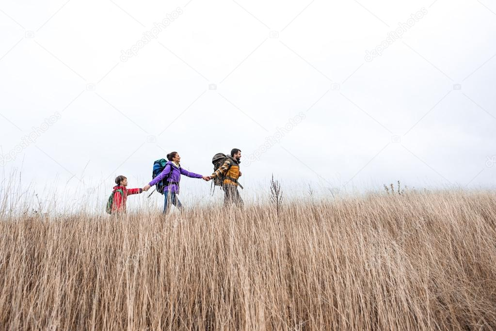 Happy family with backpacks walking in grass