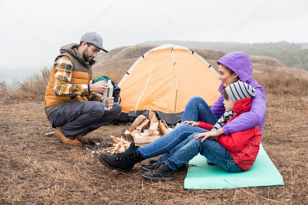 Happy young family sitting near tent