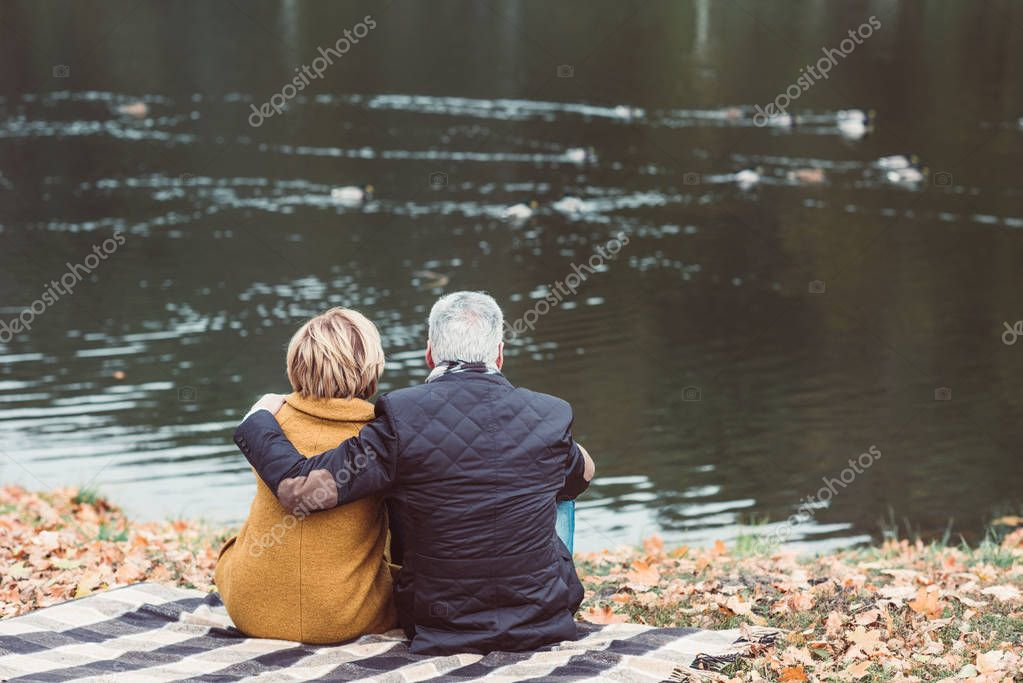 Mature couple looking on lake with ducks