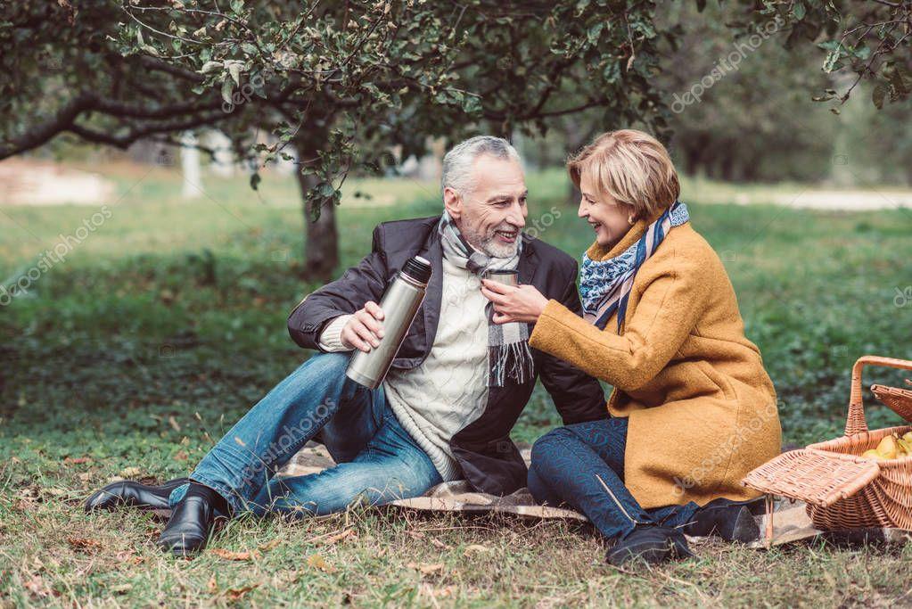 Mature couple drinking tea in park