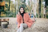 Atraktivní žena sedí v čistých swing