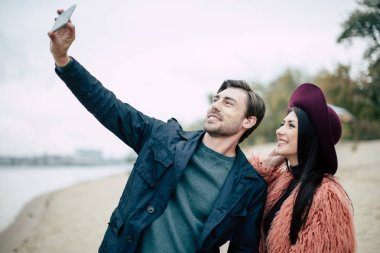 Smiling couple taking selfie on beach