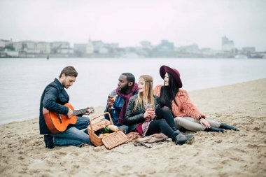 Happy young friends with guitar at picnic