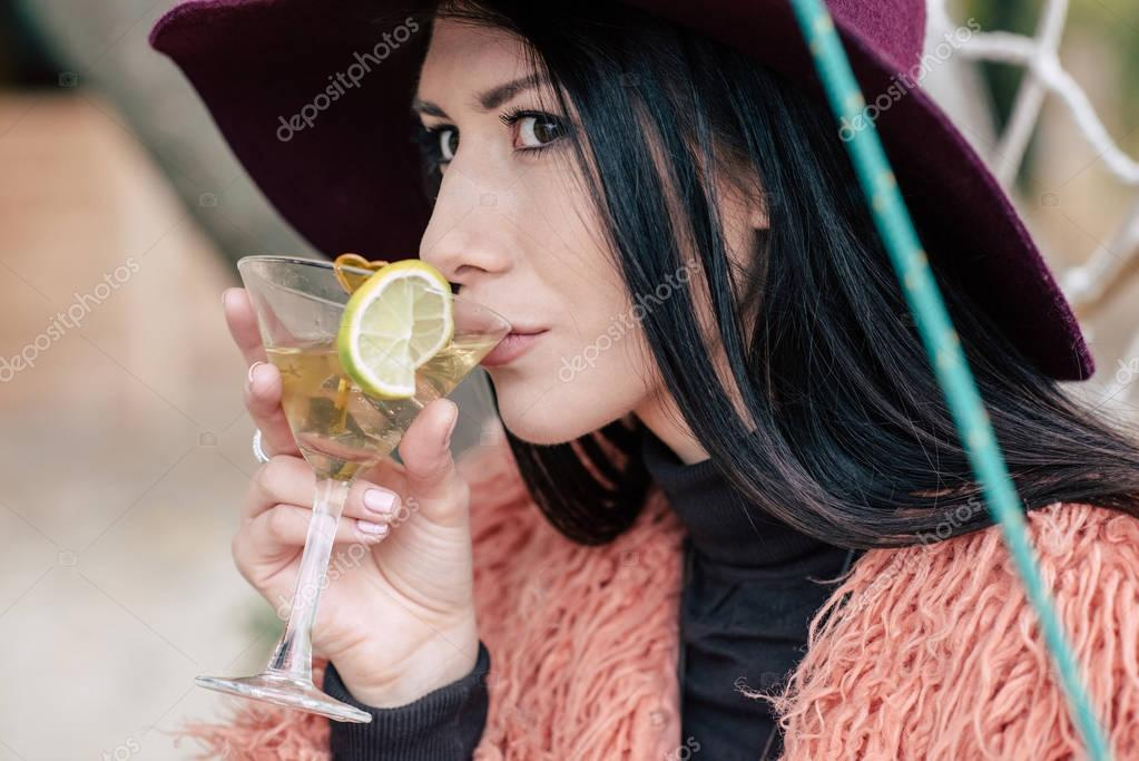 Fashionable young woman drinking cocktail