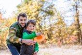 Fotografie Lächelnd, Vater und Sohn spielen mit frisbee
