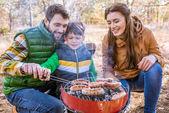 Veselá rodiče s synem grilovací klobásy