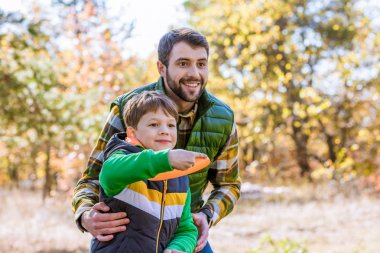 Smiling father and son playing with frisbee
