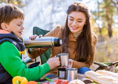 Happy mother pouring tea to son