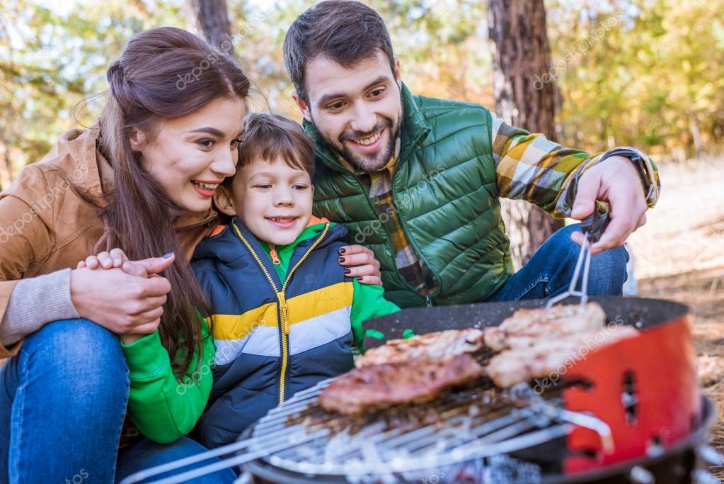 Family grilling meat on barbecue