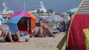Spanyolországi tengerpartjai Katalóniában. Emberek napozni a tengerparton, a forró nap