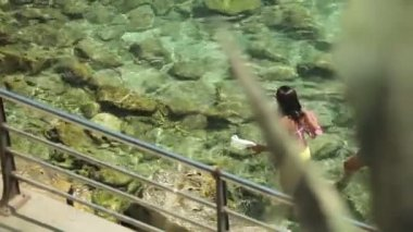 Az emberek fürdeni és pihenni a városi strand. A bikini lányok megy egy vidéki város Porto Cristo a tengerpart mentén. Mallorca
