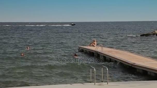 Persone fare il bagno e riposare sulla spiaggia della città