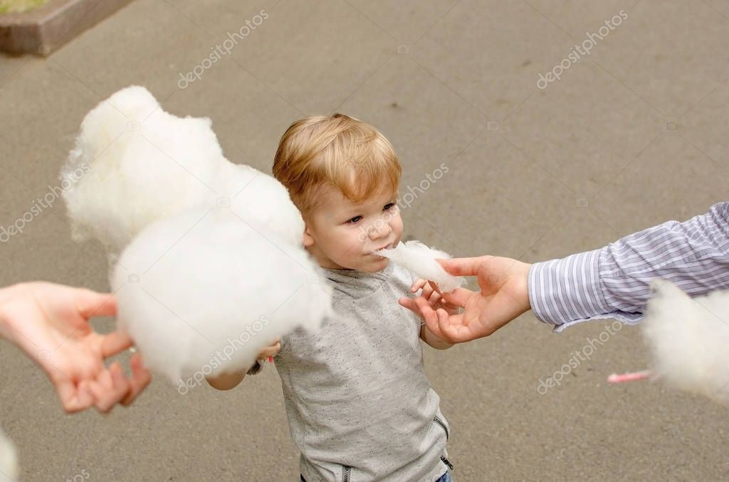 Small baby boy is eating cotton candy