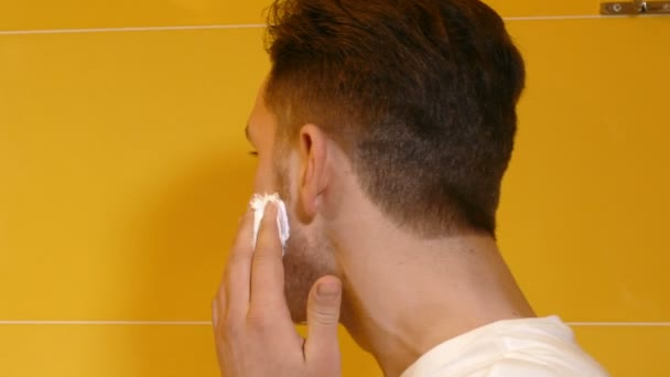 closeup of young man shaving in the bathroom