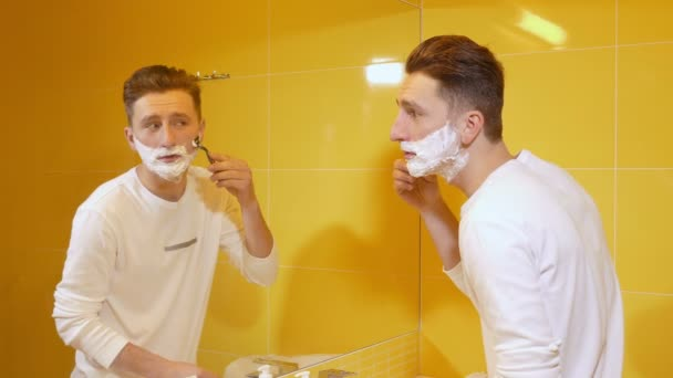 young man shaving in the bathroom in front of mirror