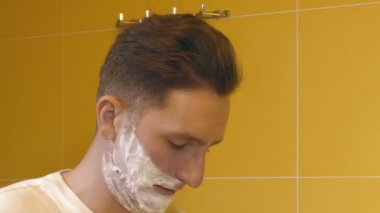 closeup of young man shaving in the bathroom in front of mirror