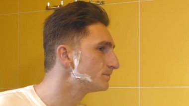 closeup of young man in the bathroom shaving