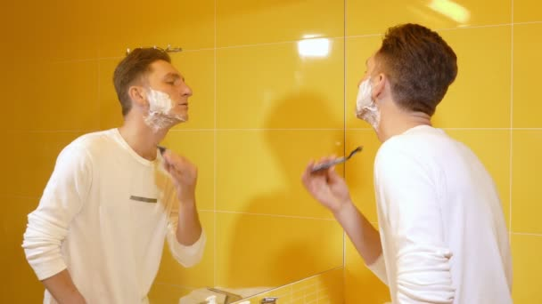 Young man shaving in yellow bathroom in the morning