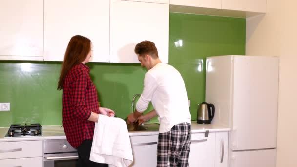 mladý pár mytí a sušení nádobí v kuchyni