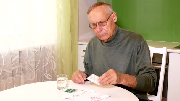 alter Mann sitzt in der Küche und entscheidet, welche Pille er nehmen soll