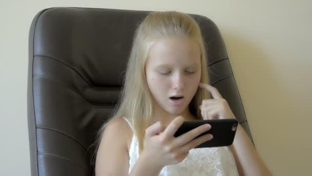 Detailní záběr na dospívající dívky sedí a hraje s mobil
