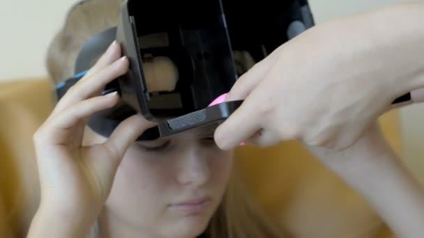 Detailní záběr na Zenske ruce s nehty pomáhá dospívající dívka použití virtuální brýle