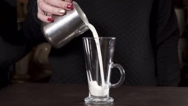 Closeup ženy nalévá mléko pro cofee do skla, pomalý pohyb