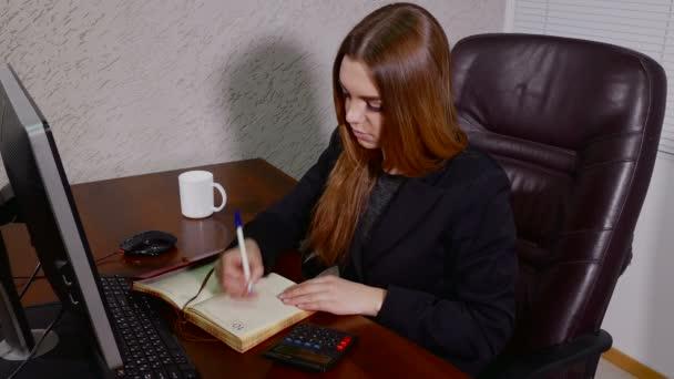 Fiatal nő jegyzetelés notebook iroda