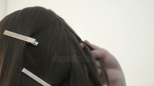 Closeup mladé kadeřnice, takže účes pro klienta v salonu