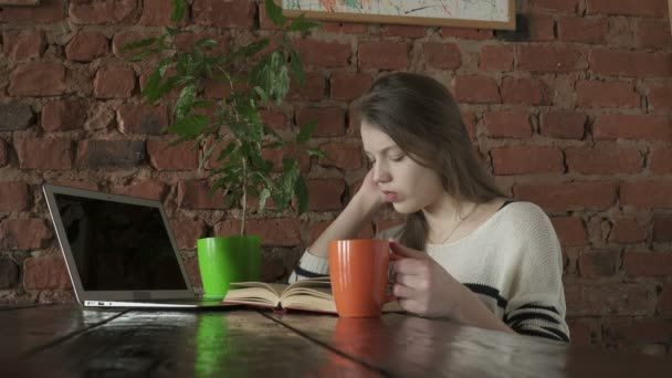 Boded teenager girl reading a book