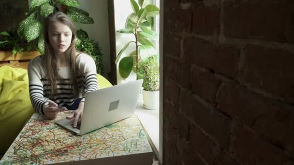 Dospívající dívka sedí a kreditní kartou pro online nakupování