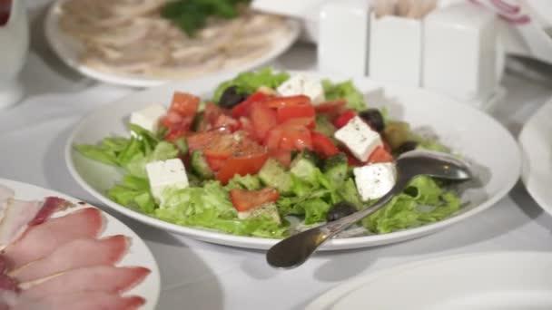 Nahaufnahme von schmackhaftem Salat und Gerichten, die auf dem weißen Teller auf dem Tisch serviert werden