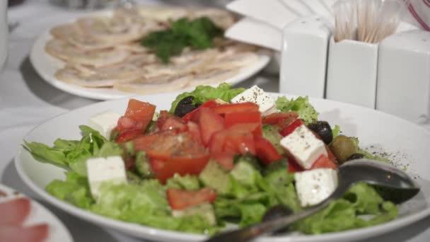 Řecký salát podávaný na bílé plotně
