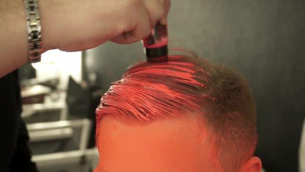 Make-up master pokrývá vlasy modely s oranžovou barvou, closeup