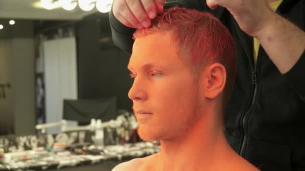Closeup make-up Master pokrývající mans vlasy barvou světlý oragne