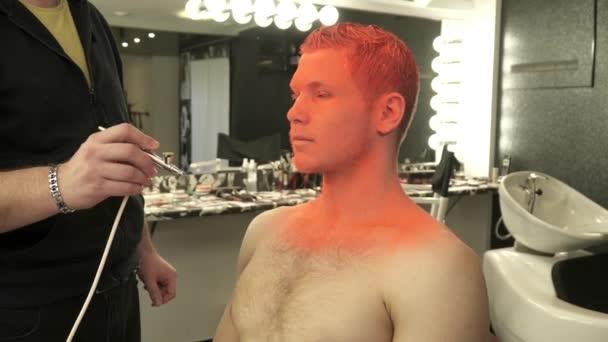 Mistr umění make-up pokrývající tělo modely s světlé barvy