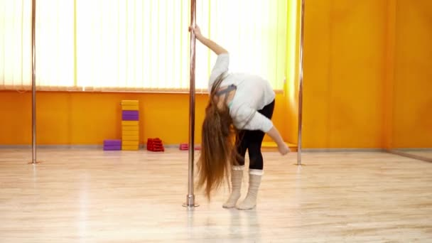 Young dancer dancing near the pole