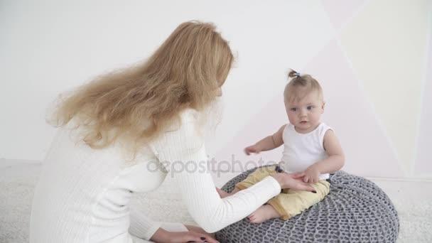 Mladá matka hrát se svým dítětem, když se sedí na upleteného
