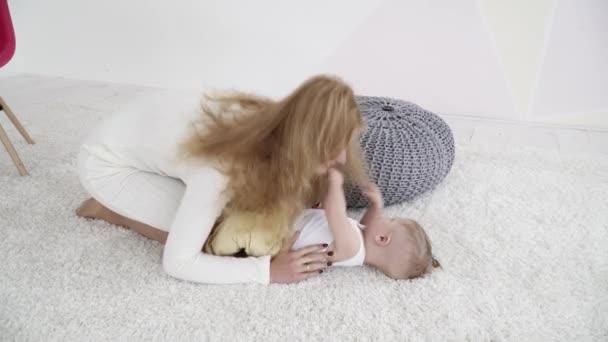 Matka, hrát si s její dítě chlapec leží na koberci