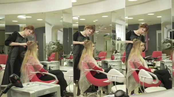 Hairdresser combing womans hair in a beauty salon