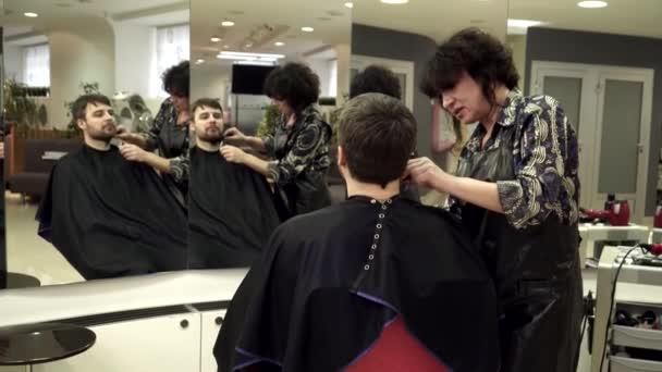 Hairdreser vágás mans szakáll, tükörképét a tükörben