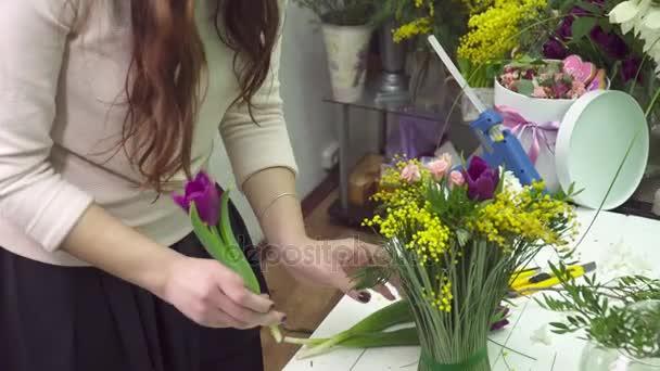 Květinářství dělá kytice s mimózy a tulipány