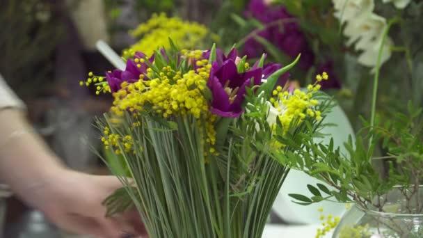 Virágüzlet mimosa és tulipán csokor a virágok hozzáadása